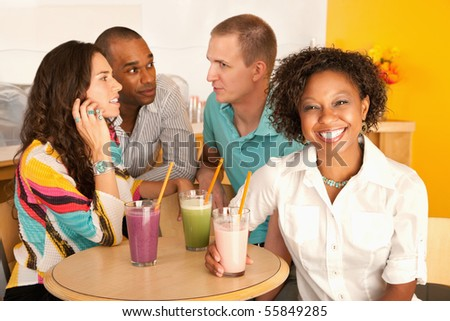 Two couples at a cafe drinking frozen beverages. Horizontal shot.