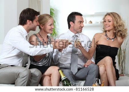 Two couples celebrating with champagne - stock photo
