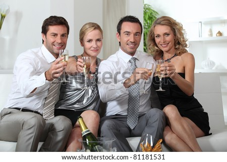Two couples drinking champagne - stock photo