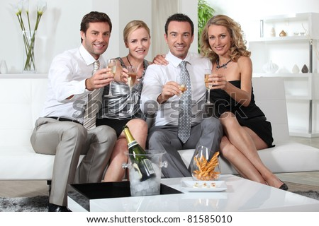 Two couples drinking champagne at home - stock photo