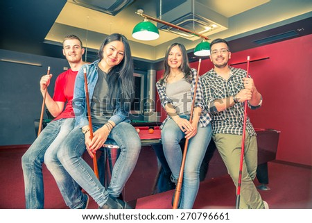 Two couples having fun at billiard - Group of multiracial young people standing next to pool table and holding cue - Students spending an evening at pub - stock photo