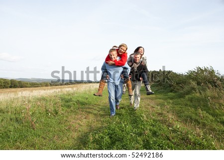 Two Couples Having Piggyback Ride In Autumn Landscape - stock photo