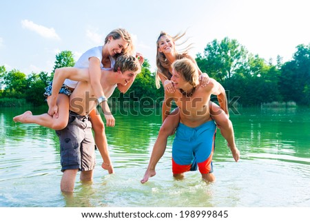 Two couples in love in the water on the beach - having some fun together splashing water at each other  - stock photo