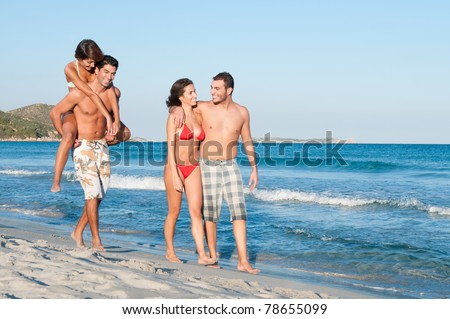 Two couples of friends walking along the beach in a summer vacation day - stock photo