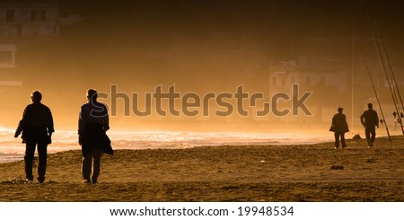 Two couples of silhouettes of men walking along a misty and orange seashore