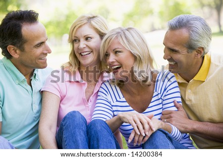 Two couples outdoors smiling - stock photo