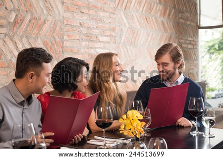 Two couples reading menu in a restaurant - stock photo