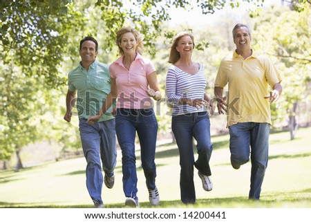 Two couples running outdoors smiling - stock photo