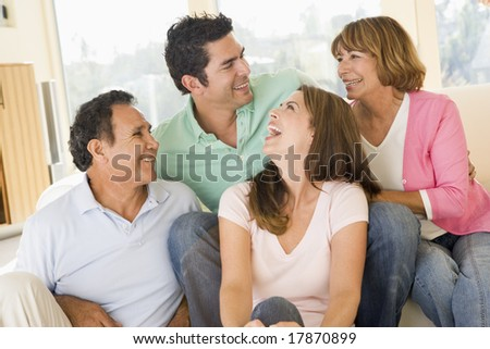 Two couples sitting in living room smiling - stock photo