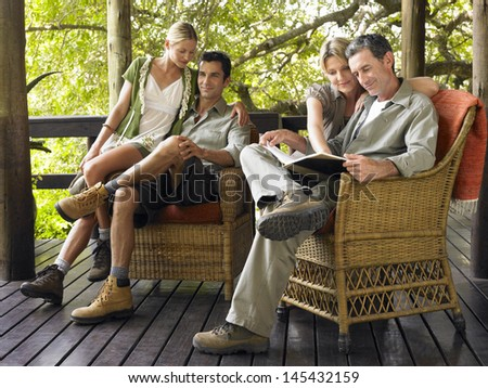 Two couples sitting in wicker chairs on terrace - stock photo
