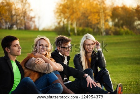 Two couples sitting on the loan in the park smiling and having fun - stock photo