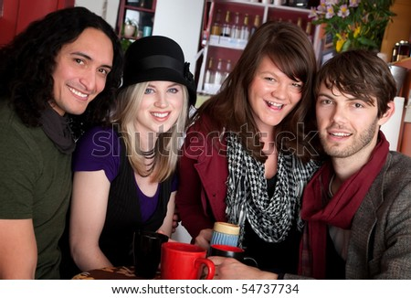 Two couples smiling together in a cafe