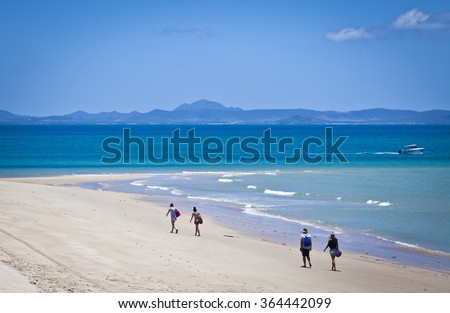 Two couples walk on an ideal beach on Keppel Island, Queensland, Australia. Sun soaked sand beside turquoise ocean at the start of the Great Barrier Reef. - stock photo