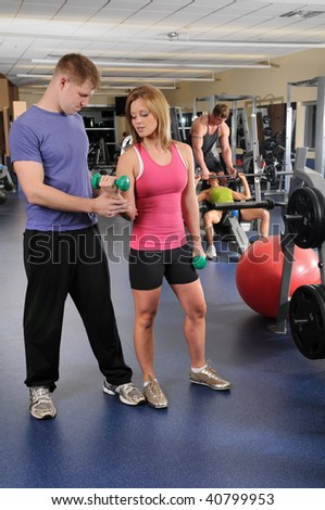 Two couples working our at gym with dumbbells and barbell