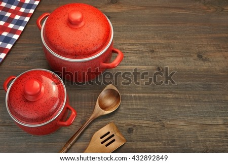 Two Covered Red Saucepan, Wooden Spatula And Spoon, Checkered Tablecloth On The Rough Rustic Brown Wood Table Background, Top View, - stock photo