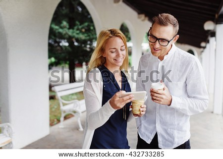 Two coworkers having a coffee break  and discussing news outside - stock photo