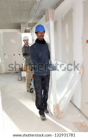 two craftsmen carrying materials - stock photo