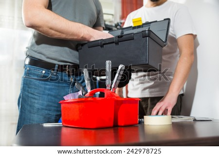 Two craftsmen take a tool from a toolbox, selective focus - stock photo