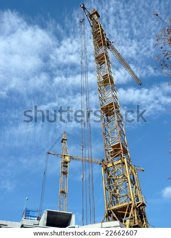 two crane towers on sky background at day