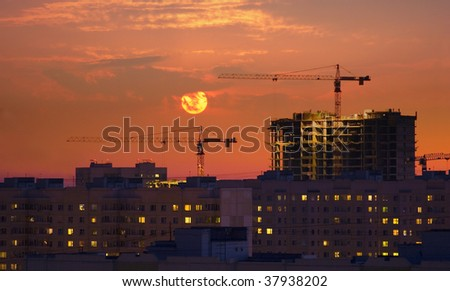 Two cranes against the setting sun in the sky of a urban city. - stock photo