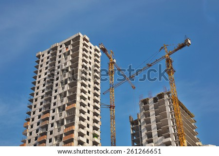 Two cranes developing residential buildings against blue sky - stock photo