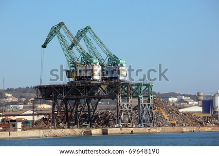 Two cranes in a huge scrapyard and big piles of metal waste
