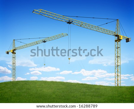 Two cranes over green hill - stock photo