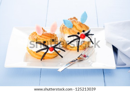 two cream puff decorated as girl bunny and boy bunny - stock photo