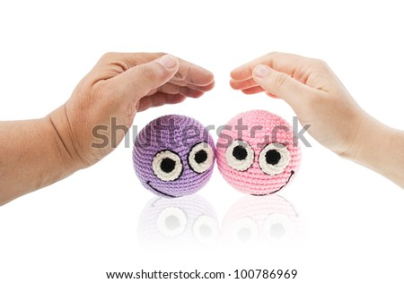 Two crochet smileys under woman and man hands protecting them. Isolated on white background. - stock photo