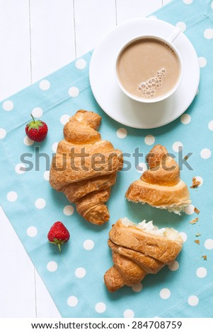 Two croissants traditional french pastry sweet dessert with a cup of coffee latte and fresh strawberry on provence style background. Perfect morning breakfast or lunch. Natural light, rustic style - stock photo