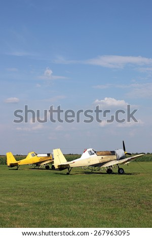 two crop duster airplanes on airfield - stock photo