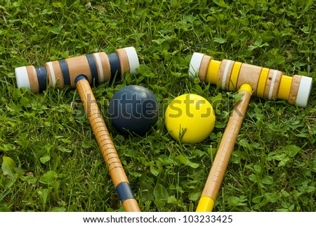two croquet mallets and balls on a grassy background - stock photo