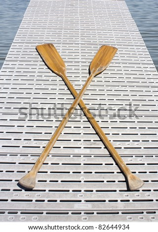 Two crossed boat oars on a dock - stock photo