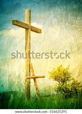Two crosses on a hill top / Following Jesus Christ / Small cross leaned toward a large cross. Color photo with a grungy wall texture. - stock photo