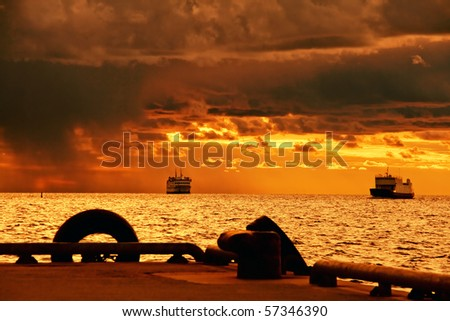 Two cruise ships from stormy sea arriving at the port during sunset - stock photo
