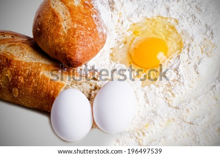 Two crusty loaves of bread next to flour and eggs. - stock photo