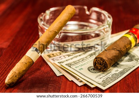 Two cuban cigars with glass ashtray on a several dollar bills on the table