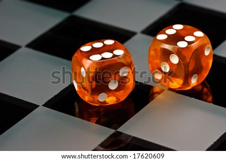 Two cube amber dice with rounded corners on checkered board - stock photo