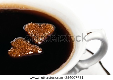 Two cubes of heart-shaped sugar floating in a cup of coffee - stock photo