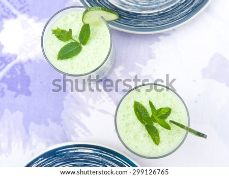 Two cucumber/mint smoothies on a table shot from above