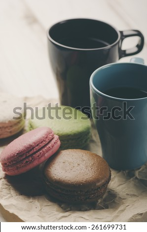 Two cup of coffee and colorful macaroons. Retro filter. - stock photo