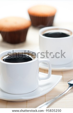 Two cup of hot coffee with muffins in the background - stock photo