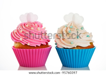 Two cupcakes in a pink and blue baking cups with pink and white cream, with decoration and two heart on the top on white background as a studio shoot