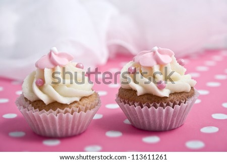 two cupcakes on pink background