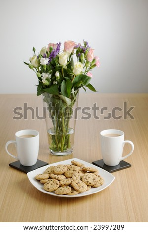 Two cups and a plate of cookies with flowers in the background.