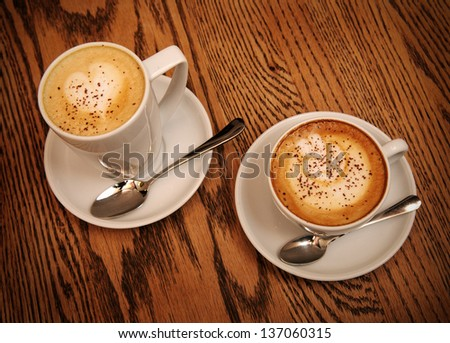 two cups cappuccino and latte on wooden table in cafe