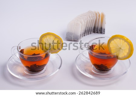 Two cups of black tea with lemon and tea bags. - stock photo