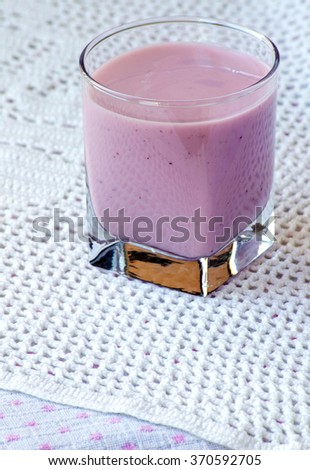 Two cups of blueberry yogurt with blueberries close up on a table