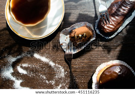 two cups of coffee and chocolate cream puff on a dark wooden table, for calendars, illustrations - stock photo