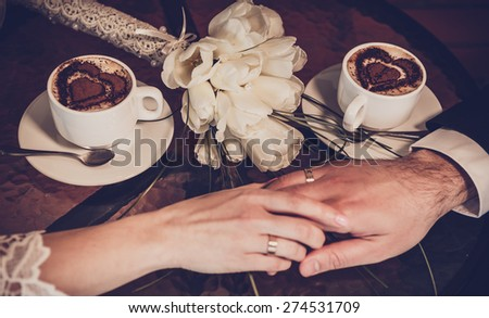 Two cups of coffee and hand of bride and groom with wedding rings - stock photo